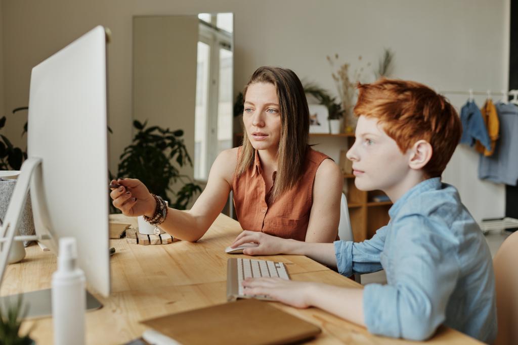 woman teaching son computer